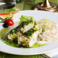 white fish with pesto sauce and meat on a plate in a still life gourmet restaurant menu